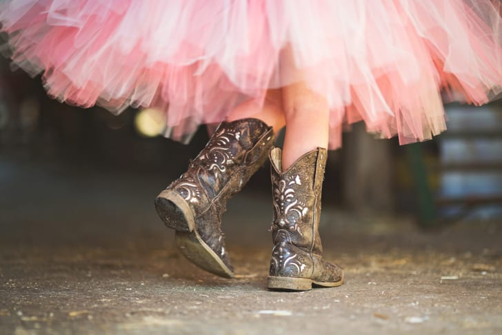 The lower half of a person in a pink tutu and cowgirl boots