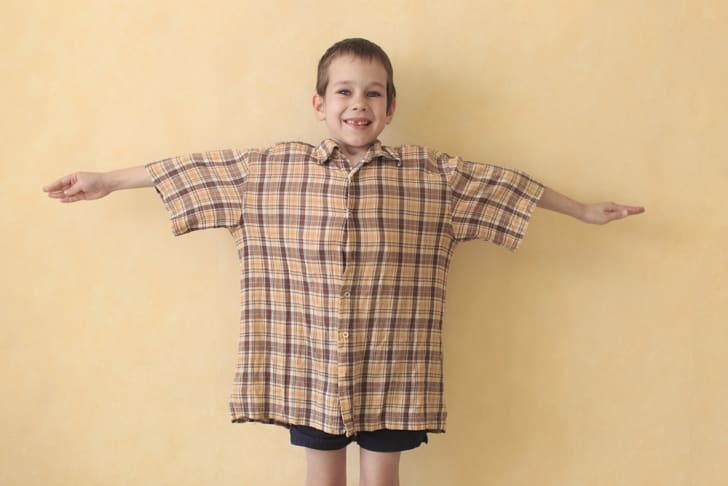 A little boy with his arms spread out, wearing an oversized t-shirt