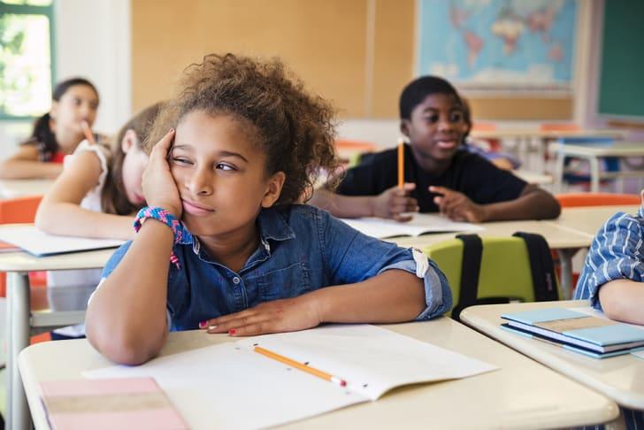A bored little girl in an elementary classroom