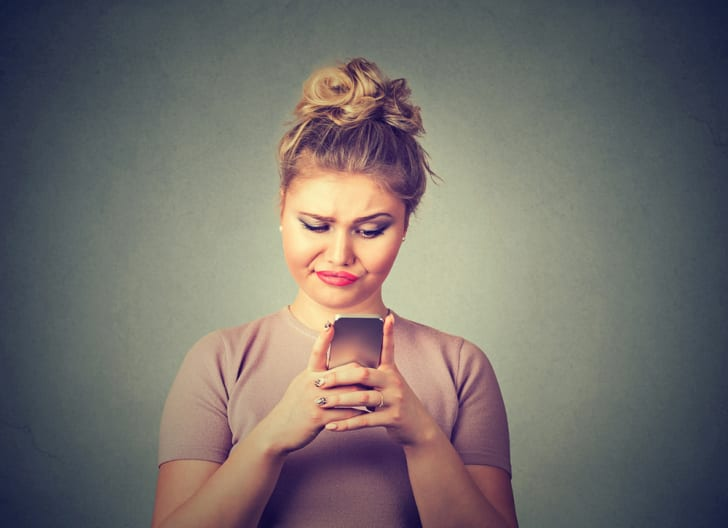 A skeptical woman texting on a phone
