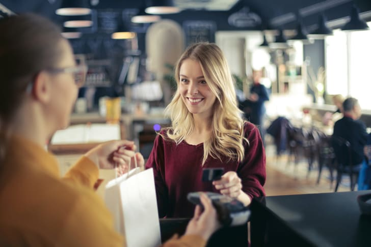 A young blond woman paying with a credit card at a shop