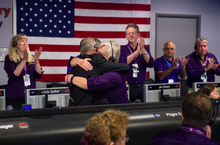 Cassini team members Earl Maize (left) and Julie Webster embrace after the spacecraft plunged into Saturn.
