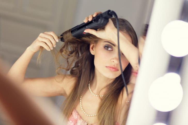 Woman using curling iron to curl her hair
