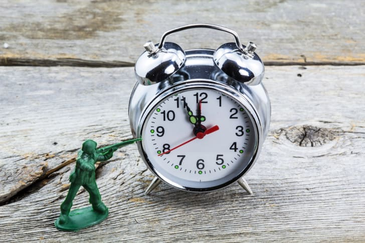 Photo of a toy soldier aiming at an alarm clock