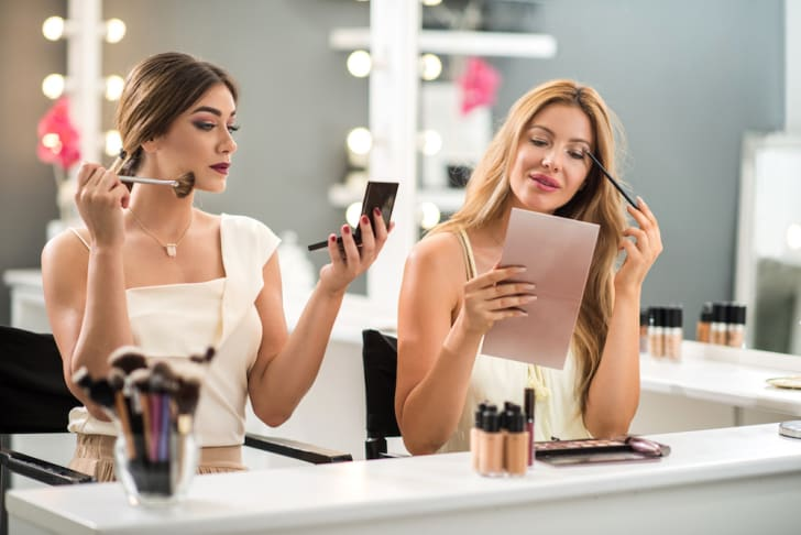 Photo of two women putting on makeup