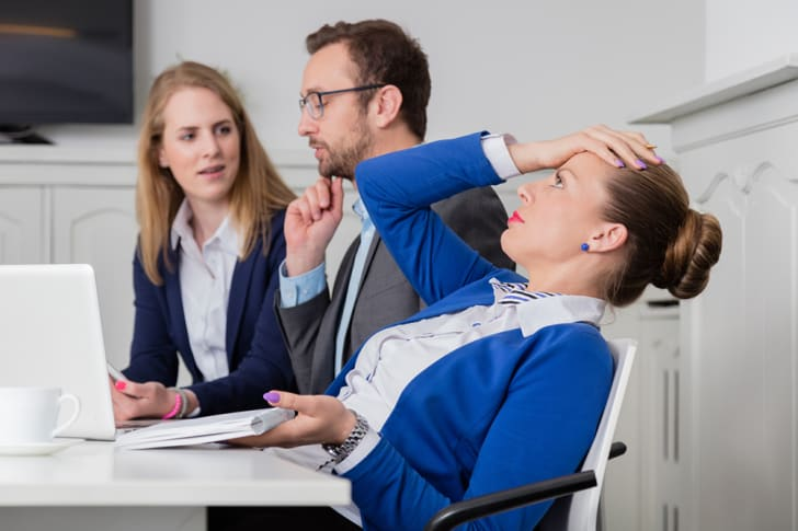 A frustrated-looking businesswoman at a meeting, leaning back in chair with her hand on her head