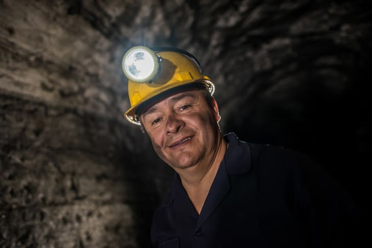 A smiling man wearing a head lamp working at a mine
