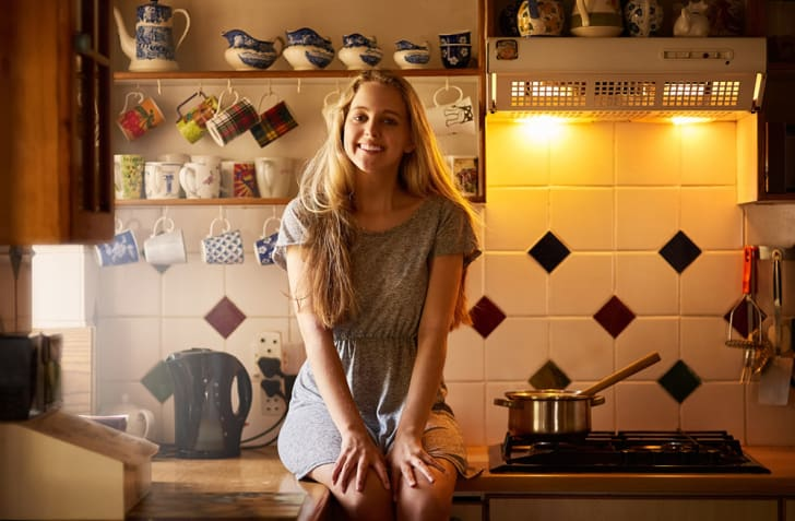 A blond woman sitting on a kitchen counter near the stove