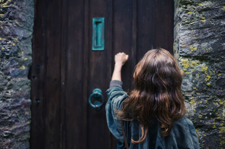 The back of a long-haired young woman knocking on a door with a blue knocker