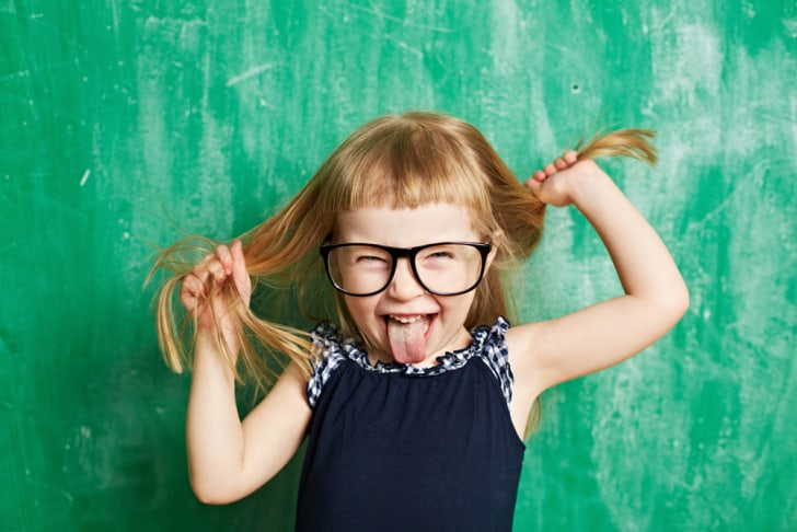 A little girl with blond hair and large black funny glasses