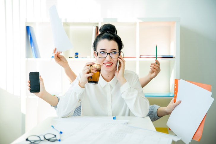 uccessful businesswoman multitasking with six arms at once, holding various implements