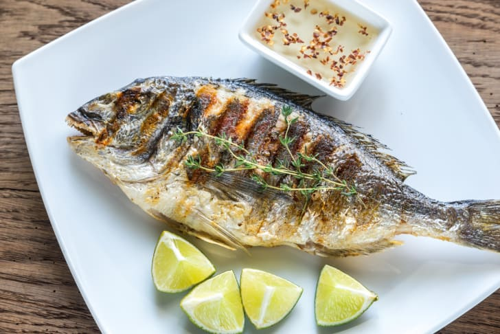 A whole grilled fish on a plate with lemons.