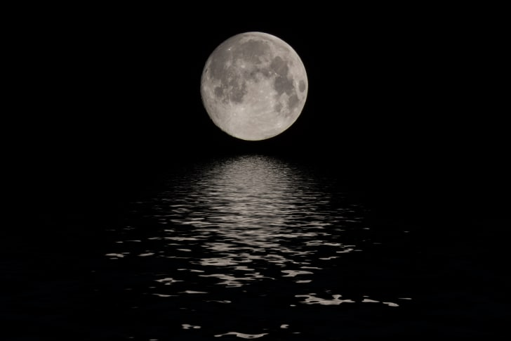 Full moon rising over a body of water.