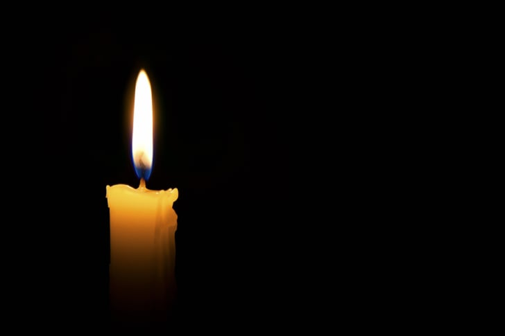A single candle burning on a black background.