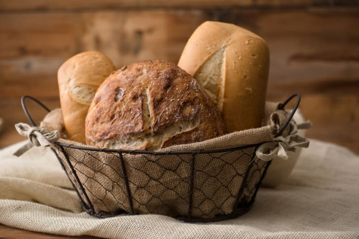 Three loaves of bread in a wire basket.