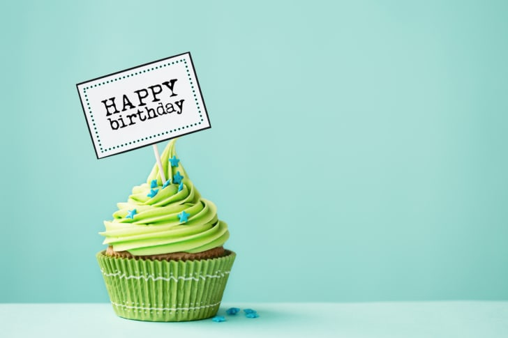 A cupcake with green icing and a sign reading 'happy birthday' stuck in it.