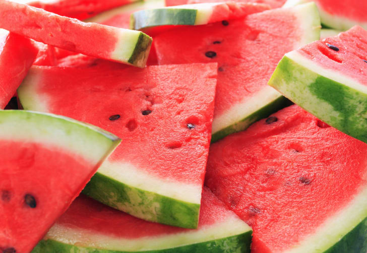 Slices of watermelon stacked in a pile.