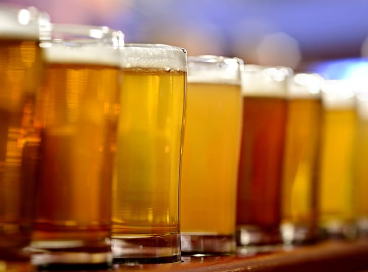 A row of different beers in glasses on a bar.