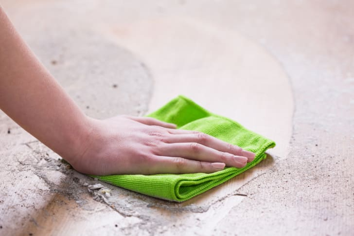 A person wiping up dust with a cloth.