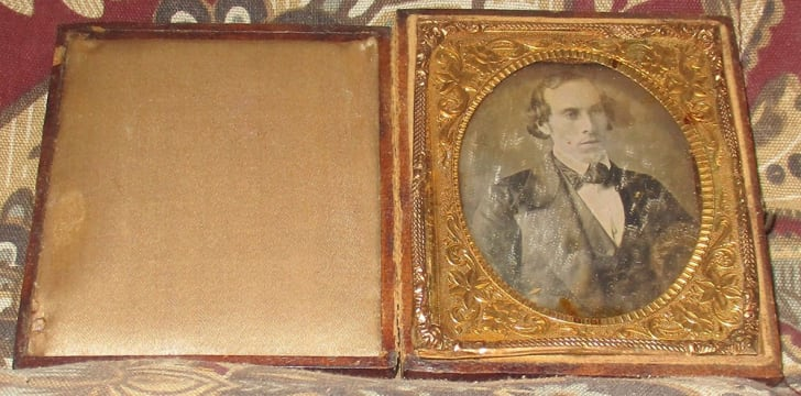 A historic daguerreotype is open to show a man in a suit.