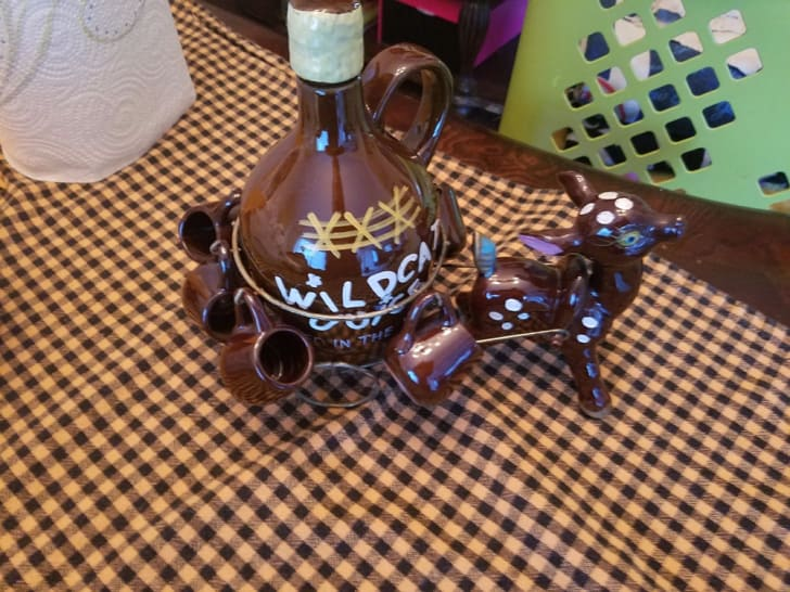 A small decorative brown jug with a donkey pulling it is set on a checkered tablecloth.