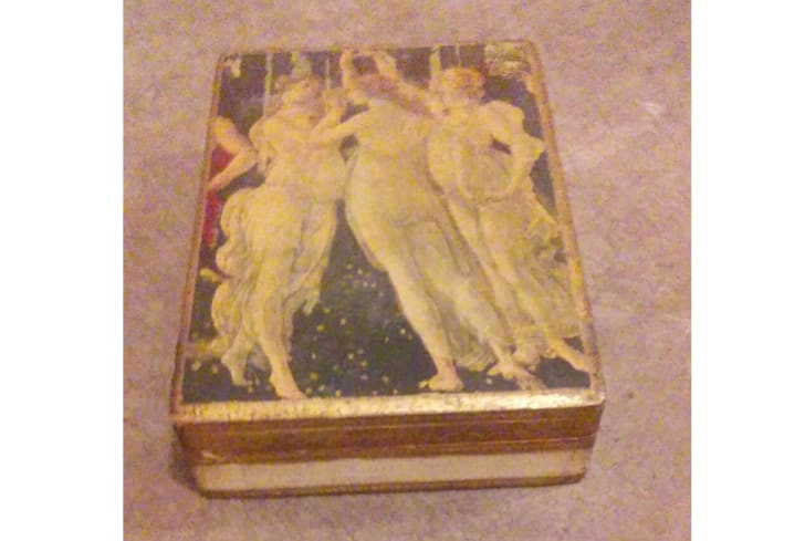 A wooden box with a classical piece of art depicting nude women on top