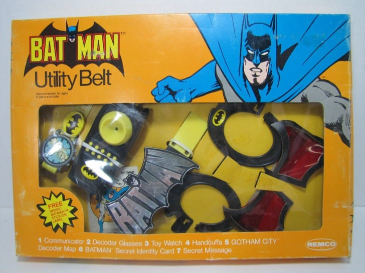 A vintage Batman utility belt stilli n packaging, with plastic handcuffs, decoders, and watch.
