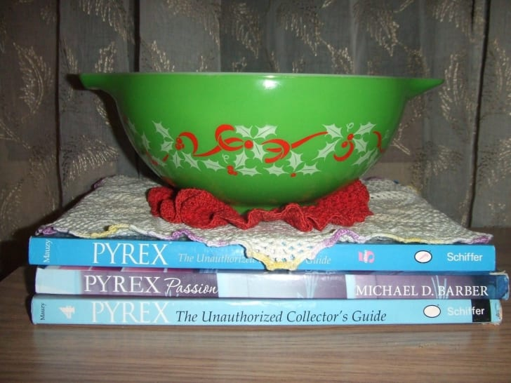 A green Pyrex mixing bowl with red ribbons and holly on it, sitting on top of three pyrex collecting books.