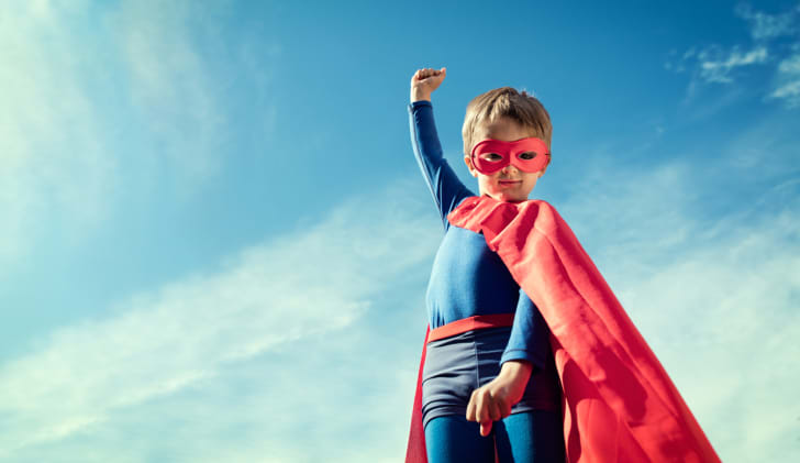 A little boy in a superhero outfit with a red cape.
