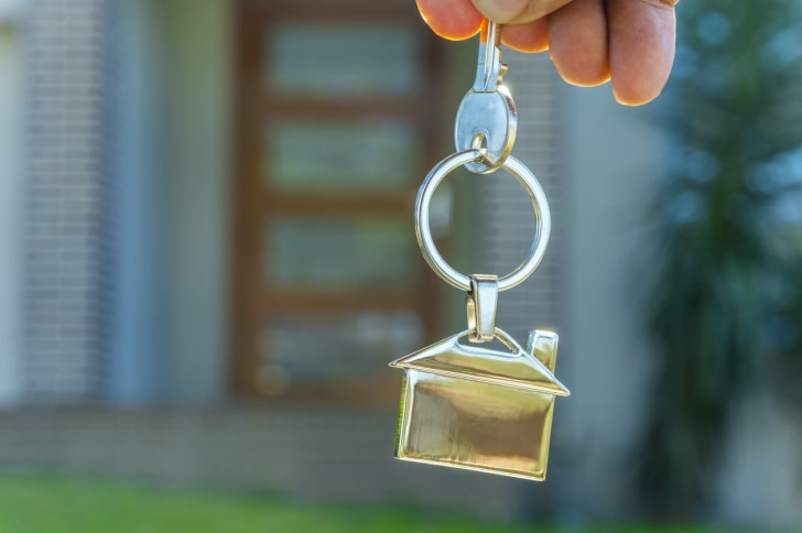 A person handing over the keys of a house.