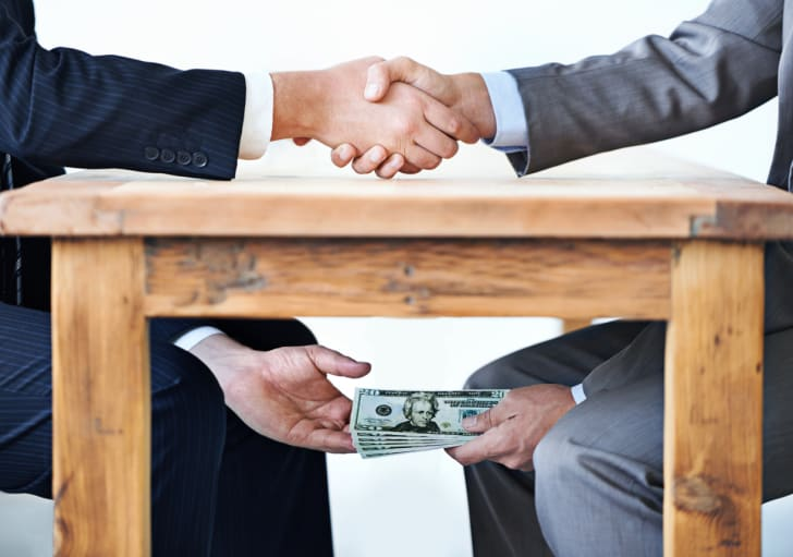 Two businessmen shaking hands over a table as they exchange money beneath it.
