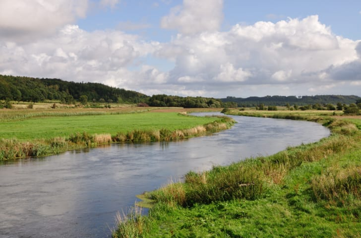 A river runs through a green field.