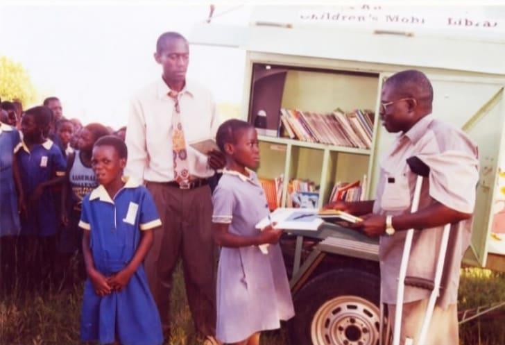 Kids getting books from a cart.