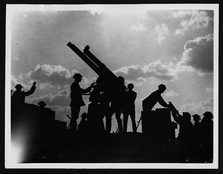 Soldiers silhouetted against the sky, preparing to fire an anti-aircraft gun