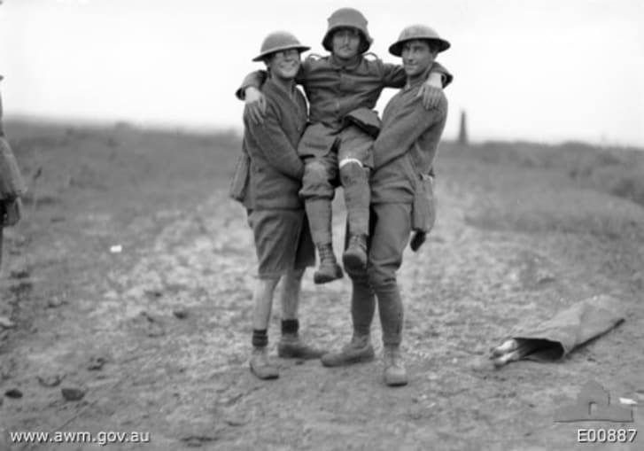 Two Australians assist a prisoner, who was severely wounded in the leg, near Anzac Ridge