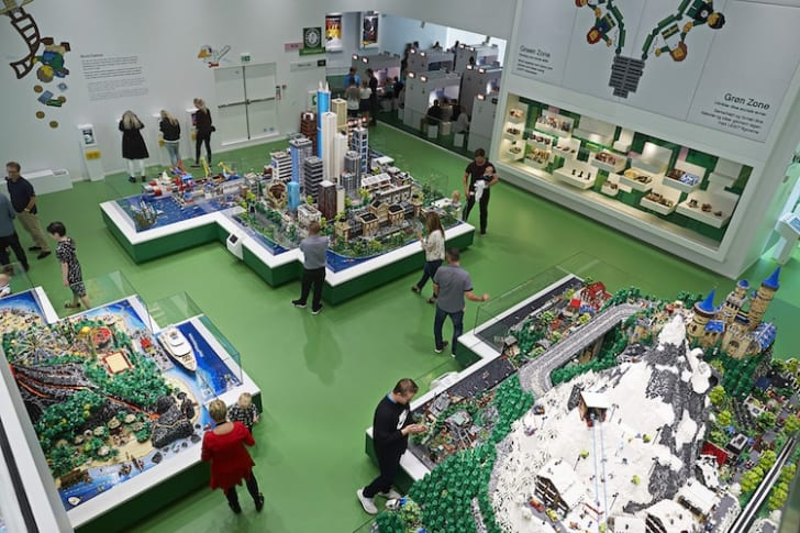 Kids visiting the LEGO House in Billund, Denmark, play with LEGOs in the World Explorer section, which has three themed islands filled with LEGO mini-figures.
