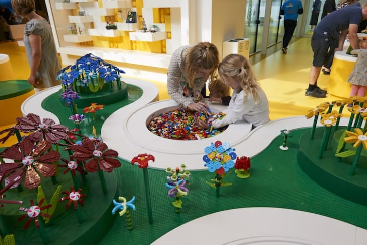 Children build LEGO flowers to plant in a special LEGO meadow at the LEGO House in Billund, Denmark.