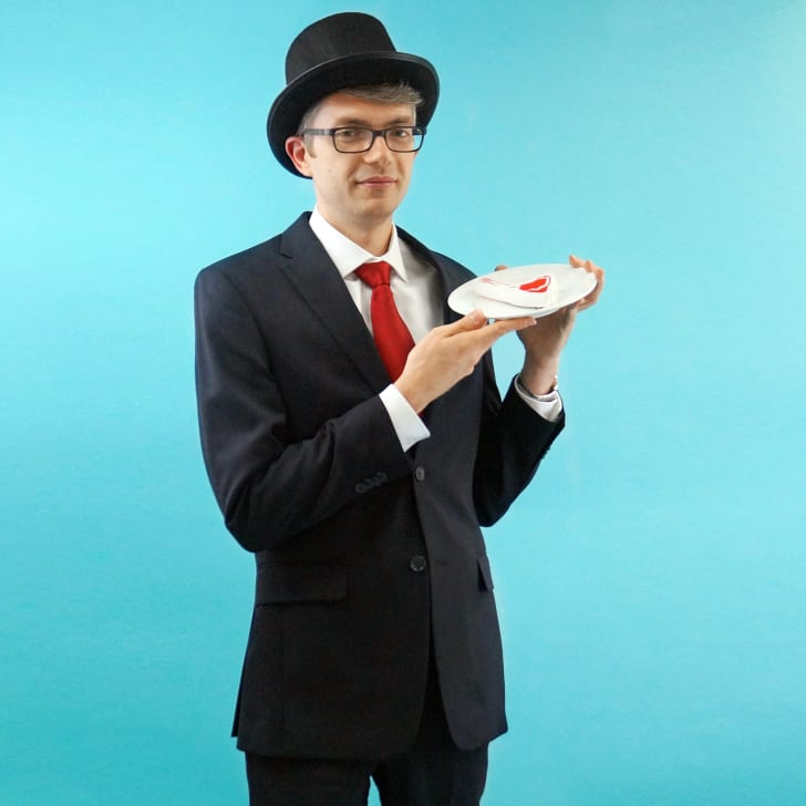 A man in a suit and top hat holding a steak.