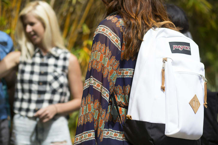 A woman wears a white JanSport backpack
