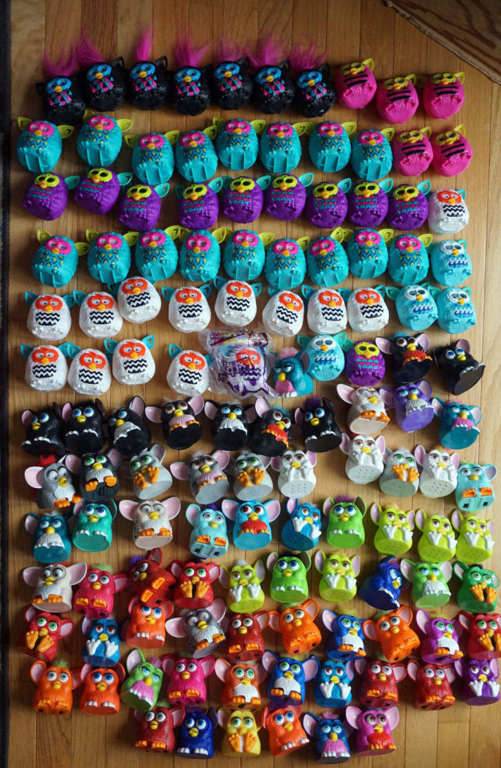 126 mini Furby toys laid out in rows on a wooden table.