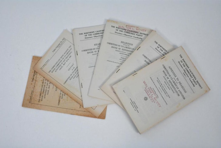 Six Cold War-era booklets spread out on a table.