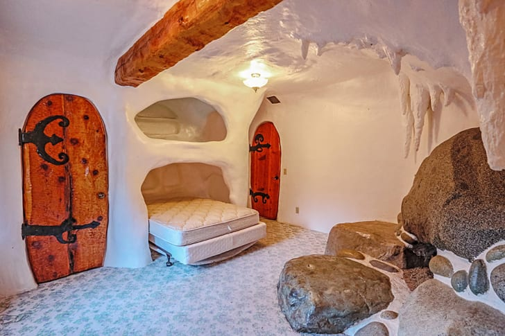 A bedroom has a mattress tucked into a cave-like nook.