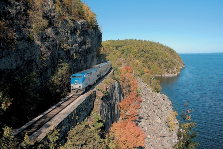 An Amtrak car runs along a cliff during the fall.
