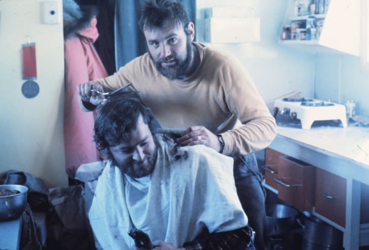 A barber gives a man a haircut in Antarctica