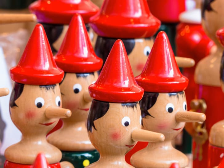 Rows of little wooden dolls with red pointed caps and extended noses.