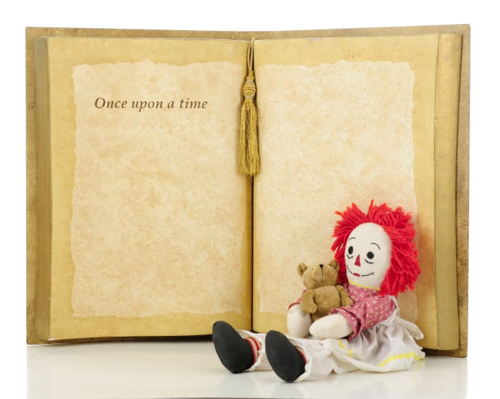 """A rag doll with red yarn hair and holding a tiny teddy bear is sitting in front of an open book that reads """"Once upon a time..."""""""