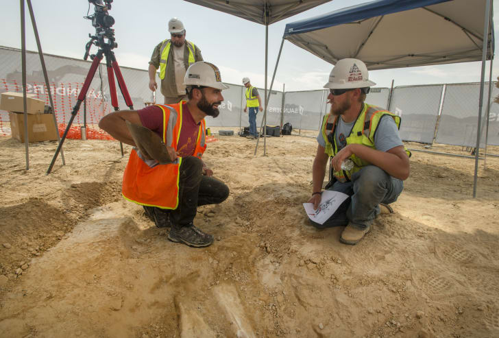 Joe Sertich, curator of dinosaurs at the Denver Museum of Nature & Science, speaks with a construction worker while leading the excavation in Thornton, Colorado of a newly discovered triceratops skeleton.