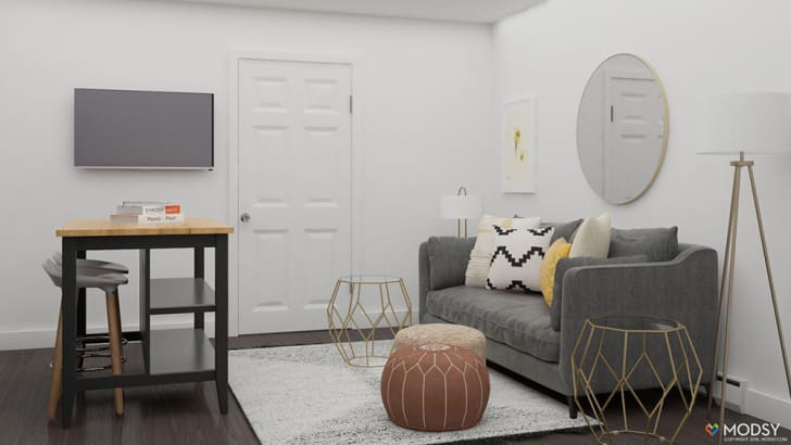 A digital rendering shows a room with a kitchen island on one side and a gray couch against a wall.