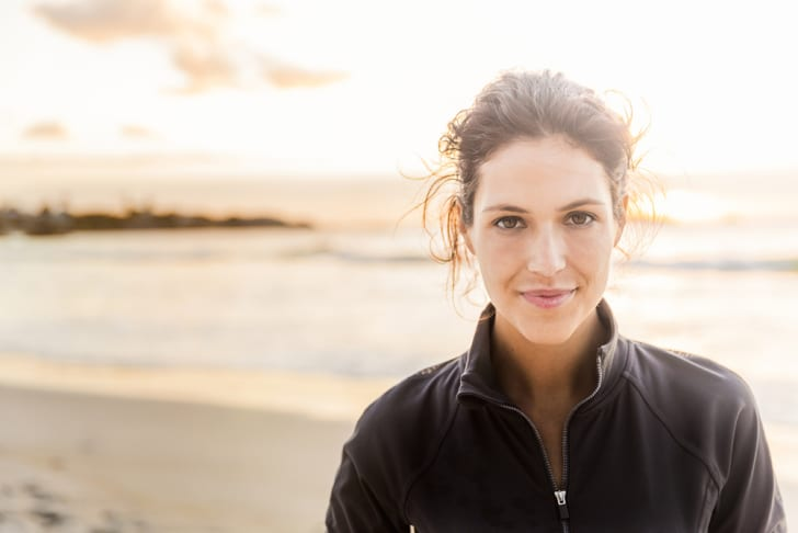 A sporty young woman on a beach looking directly at the photographer