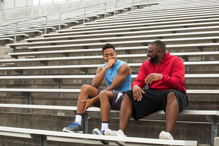 Two black men in sporty clothing sitting on bleachers and laughing